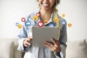woman holding tablet with emoji reactions
