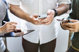 three people holding cell phones and a tablet