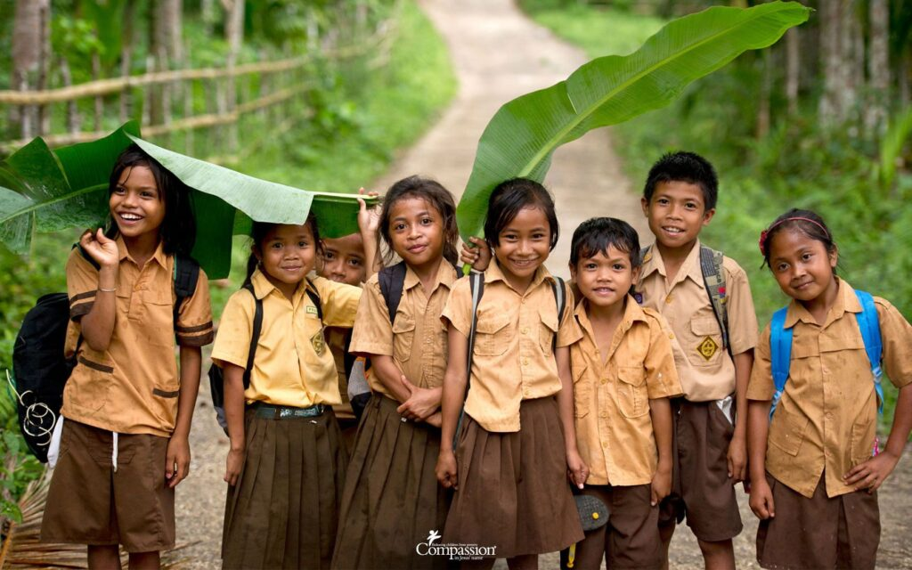 Group of young children in school uniforms, smiling